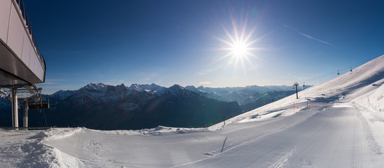 panorama view of a ski area with ski lifts and freshly groomed ski slopes on a beautiful winter day in the Alps