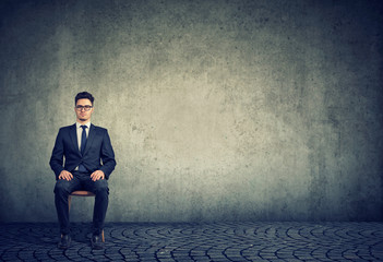 Serious businessman sitting on gray background