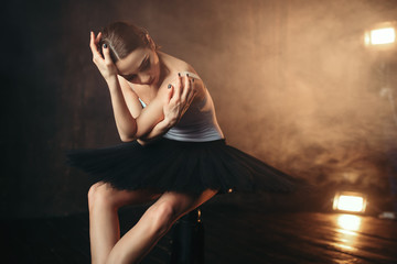 Ballerina sitting on black banquette in theatre