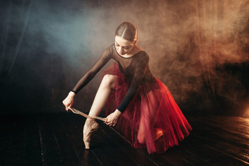 Ballet dancer tying pointe shoes