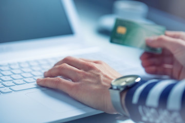 Woman hands typing on the keyboard of laptop holding credit card, close-up of online shopping