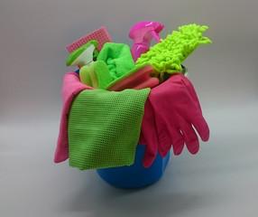 Putzeimer gefüllt mit pink und grünen Putzutensilien