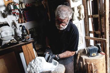 Senior man working on marble sculpture in his workshop.