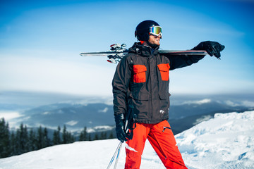 Skier with skis and poles in hands, winter sport