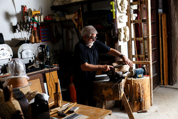 Senior man working on his wooden sculpture in his workshop.