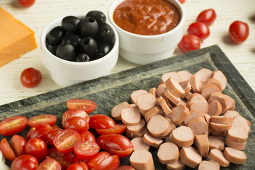 Ingredients for Italian pizza with cheddar cheese, mushrooms, black olives and sausage on white wooden background