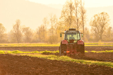 Farmer plowing soil at sunset in spring time