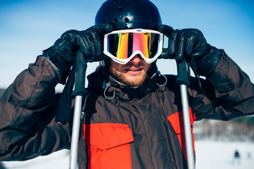 Male skier in helmet puts on glasses, front view