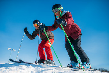 Male and female skiers racing from the mountain