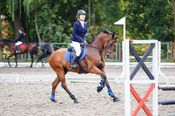 Young girl riding sorrel horse on show jumping competition