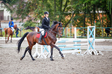 Young girl riding bay horse on show jumping competition