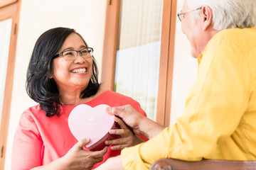 Asian senior couple in love smiling while holding together a blank heart shape