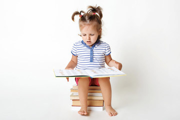Portrait of small adorable child sits on pile of books, holds interesting book, views pictures, tries to read some words, prepares for school, isolated over white background. Clever little girl
