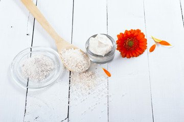 sea clay powder, moisturizer and bath salt with gerbera flower on white wooden table background