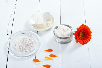sea clay powder, moisturizer and raw shea butter block with gerbera flower on white wooden table background