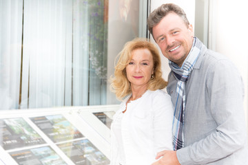 couple look at the window of a real estate agent to buy a house