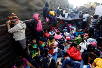 Central American migrants, moving in a caravan through Mexico, journey an open wagon of a freight train after stopping it on the rail line, in Hidalgo state
