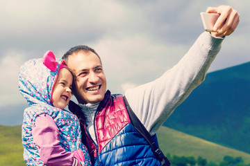 father with little daughter making selfie while hiking in summer mountains