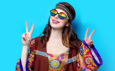 Portrait of Young hippie girl with rainbow glasses on blue background