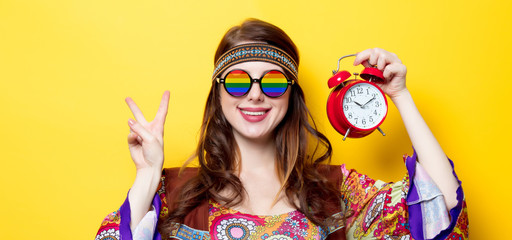 Young hippie girl with rainbow glasses and alarm clock on yellow background
