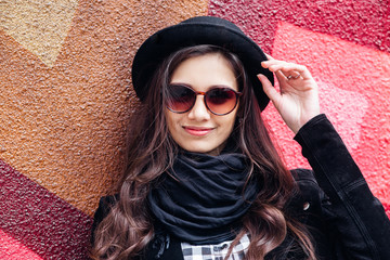 Smiling urban girl with smile on her face. Portrait of fashionable gir wearing a rock black style having fun outdoors in the city street