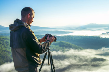 Photographer takes photos with camera on tripod on rocky mountain peak. Beautiful misty sunrise and valley view over clouds.