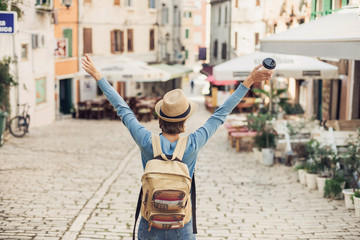 Happy tourist girl walking in the city during vacation. Cheerful woman traveling abroad in summer. Travel and active lifestyle concept
