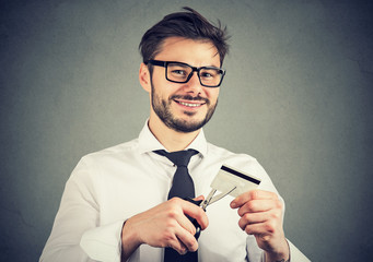 Happy man cutting credit card