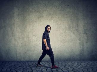 Trendy man in sportswear on gray