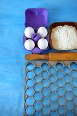 Eggs, flour and kitchen utensils for cooking homemade dumplings on blue background