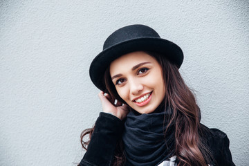 Smiling urban girl with smile on her face. Portrait of fashionable gir wearing a rock black style having fun outdoors