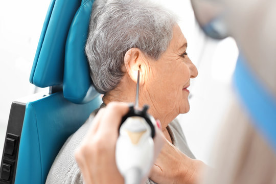 Otolaryngologist examining senior woman's ear with ENT telescope in hospital. Hearing problem
