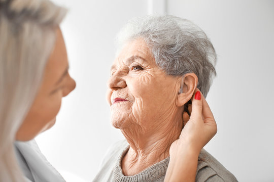 Otolaryngologist putting hearing aid in senior woman's ear on light background