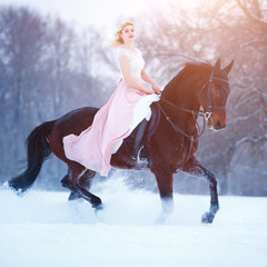 Young woman in pink dress galloping horseback on winter field. Romantic or historical equestrian background with copy space