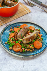 Sausage and bean casserole with carrots and green peas - top view