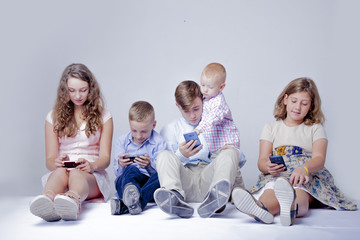 Game addiction concept. Group of friends smiling and gaming on smart phones and mobile devices.