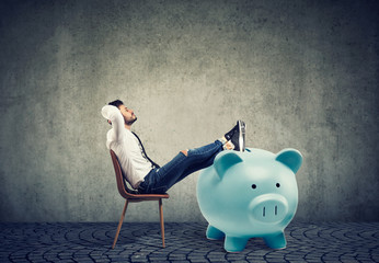 businessman with big piggy bank relaxing sitting on chair