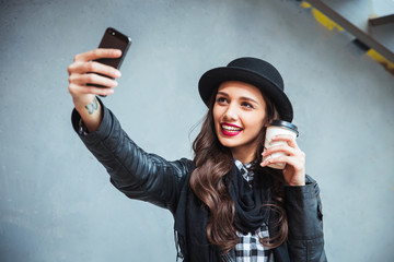 Happy young woman taking selfie. Woman taking selfie photo with a smarphone in the city street
