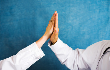 Two doctors doing high five close up