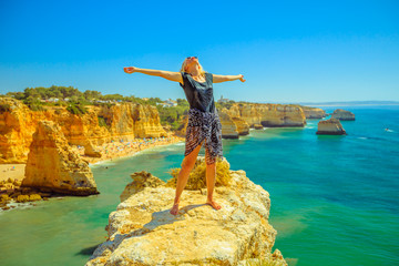 Tourism in Algarve. Freedom lifestyle tourist on promontory above scenic Praia da Marinha. Caucasian carefree woman enjoying iconic high cliffs of Marinha Beach. Summer holidays in Portugal, Europe.