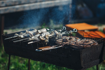 Fry the sausages on a grill outdoors. Selective focus