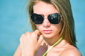 Closeup fashion beautiful woman portrait wearing sunglasses. Portrait of happy teenage girl in sunglasses with sea reflection. Summer lady