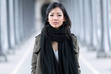 Fashion asian young woman posing and looking at camera in the street.