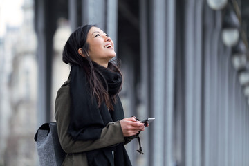 Smiling asian young woman using her mobile phone in the street.