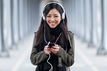 Smiling asian young woman listening to music and looking at camera in the street.