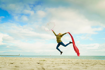 Happy woman jumping with scarf on beach