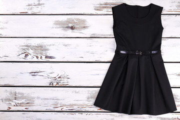 Cute toddler girls black dress. Beautiful high quality black dress for little girls, copy space. Knee-length kids black dress with belt on wooden background.