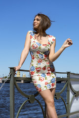 girl in short dress standing on the waterfront