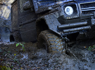 Wheel in deep rut goes through mud and leaves trail.