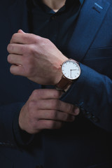 A dark portrait of a man dressed in an expensive suit, adjusting an elegant wrist watch